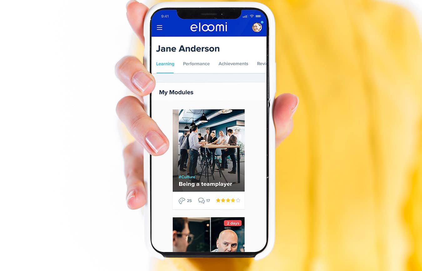 woman holding a mobile phone with eloomi platform lms module