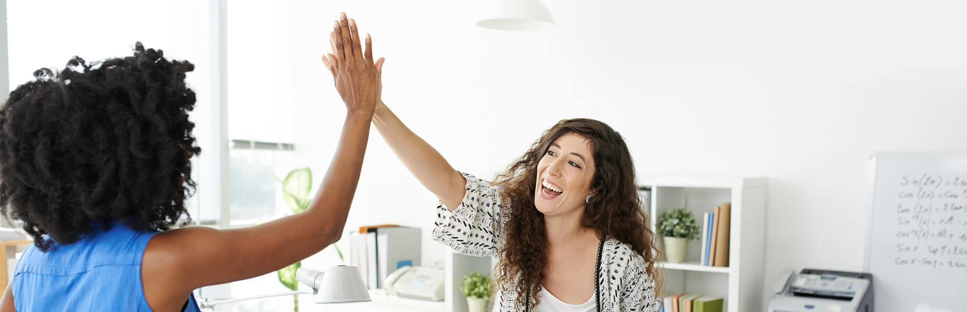 Two female employees high-fiving and celebrating
