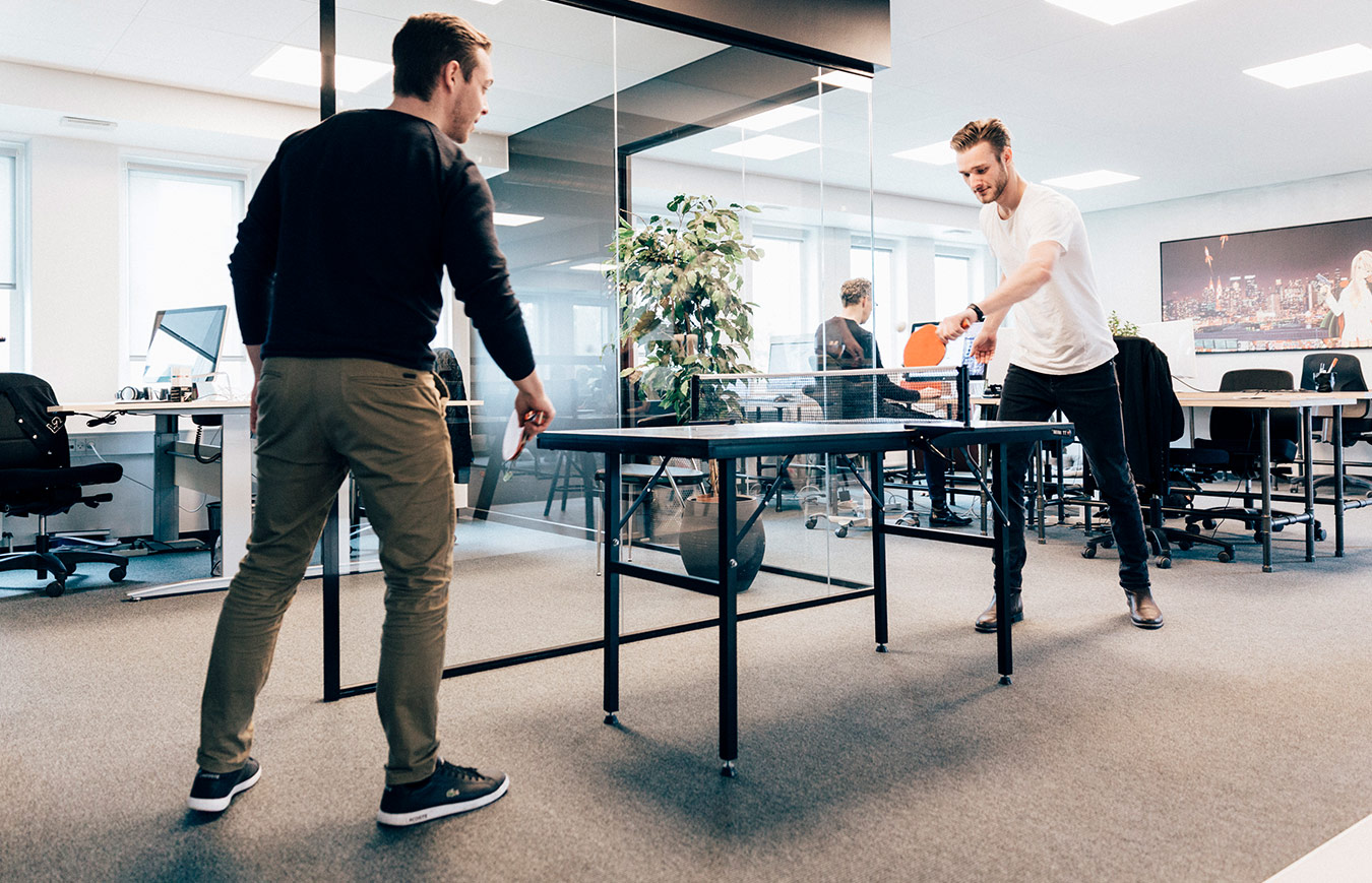 office fun - employees playing table tennis at work to relax