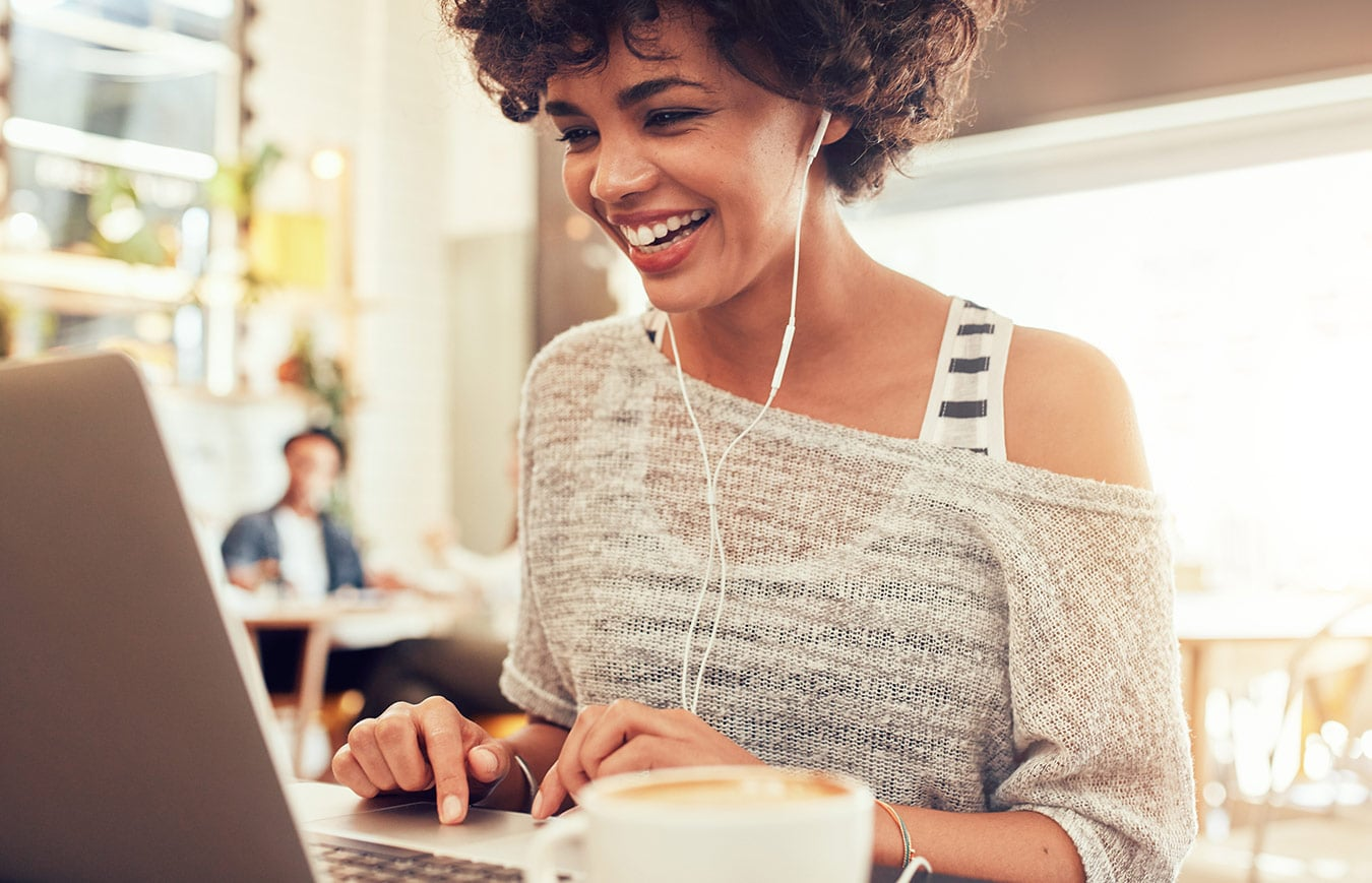 Afro-american woman sitting with a laptop and having an online course