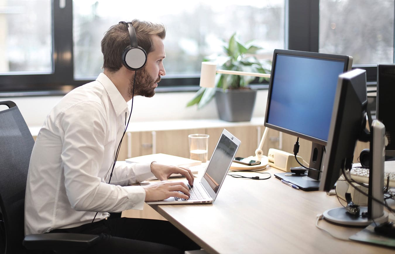 Man working at the computer and wearing headphones, taking e-learning module