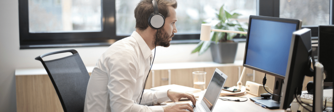 Man sitting at his desk with headphones on working on his laptop