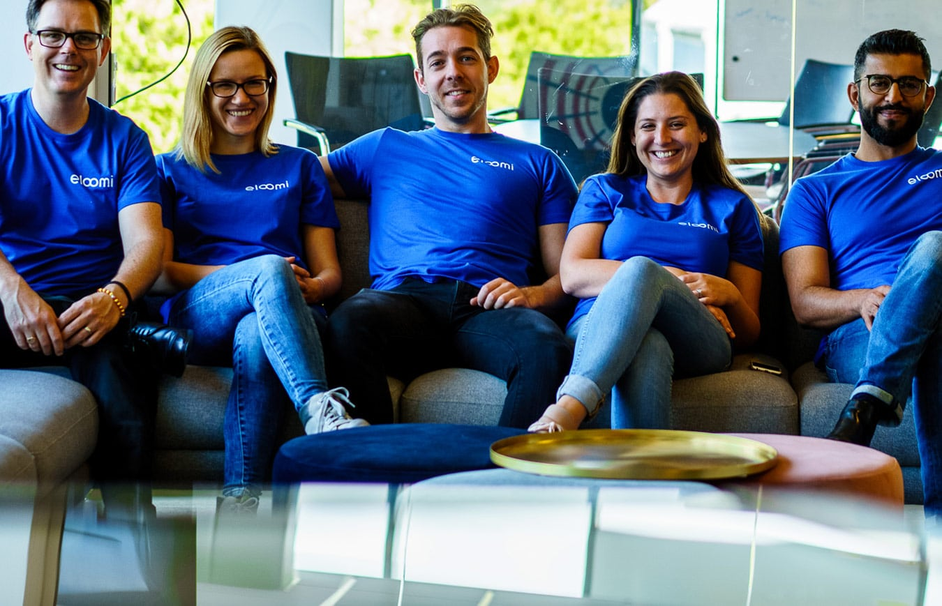 eloomi employees sitting on the sofa and wearing eloomi t-shirts