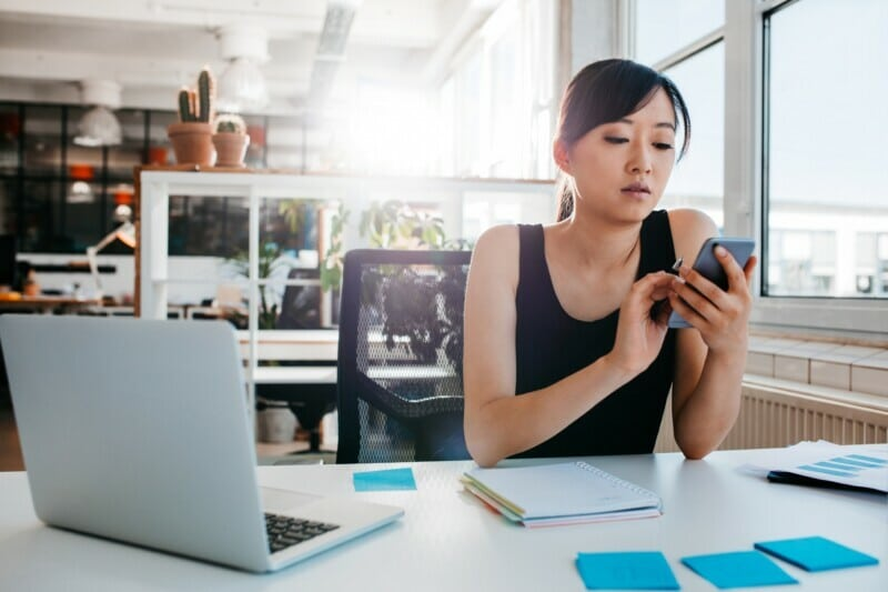Woman sitting at her desk looking at her phone