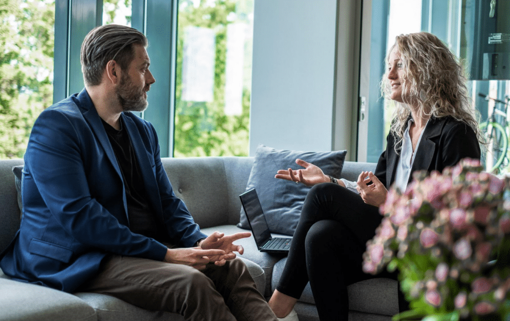 A man and woman sitting on a couch having a conversation on performance appraisal goals