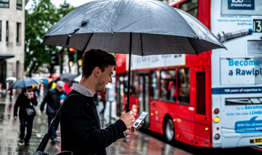 man umbrella london bus