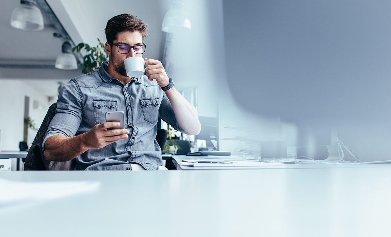A man drinking coffee and using mobile phone in the office