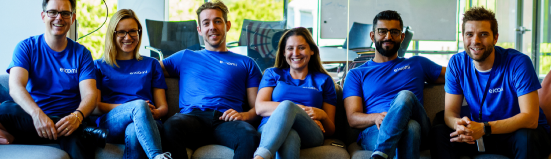 A group of eloomi coworkers sitting on a couch having a good time after an onboarding meeting