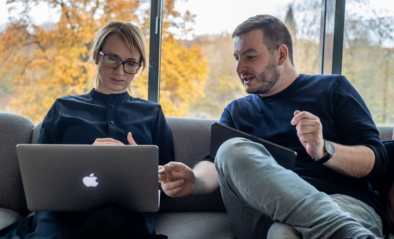 man and woman on couch with laptop in conversation